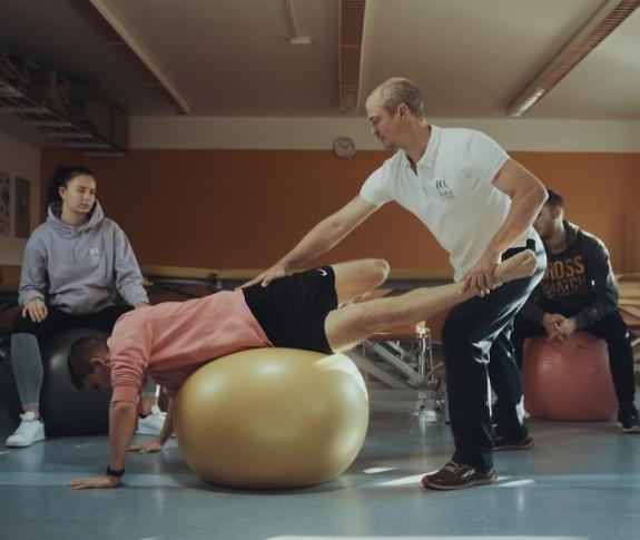 Ausbildung an der SCHULE FÜR PHYSIOTHERAPIE. Übung auf Medizinball.